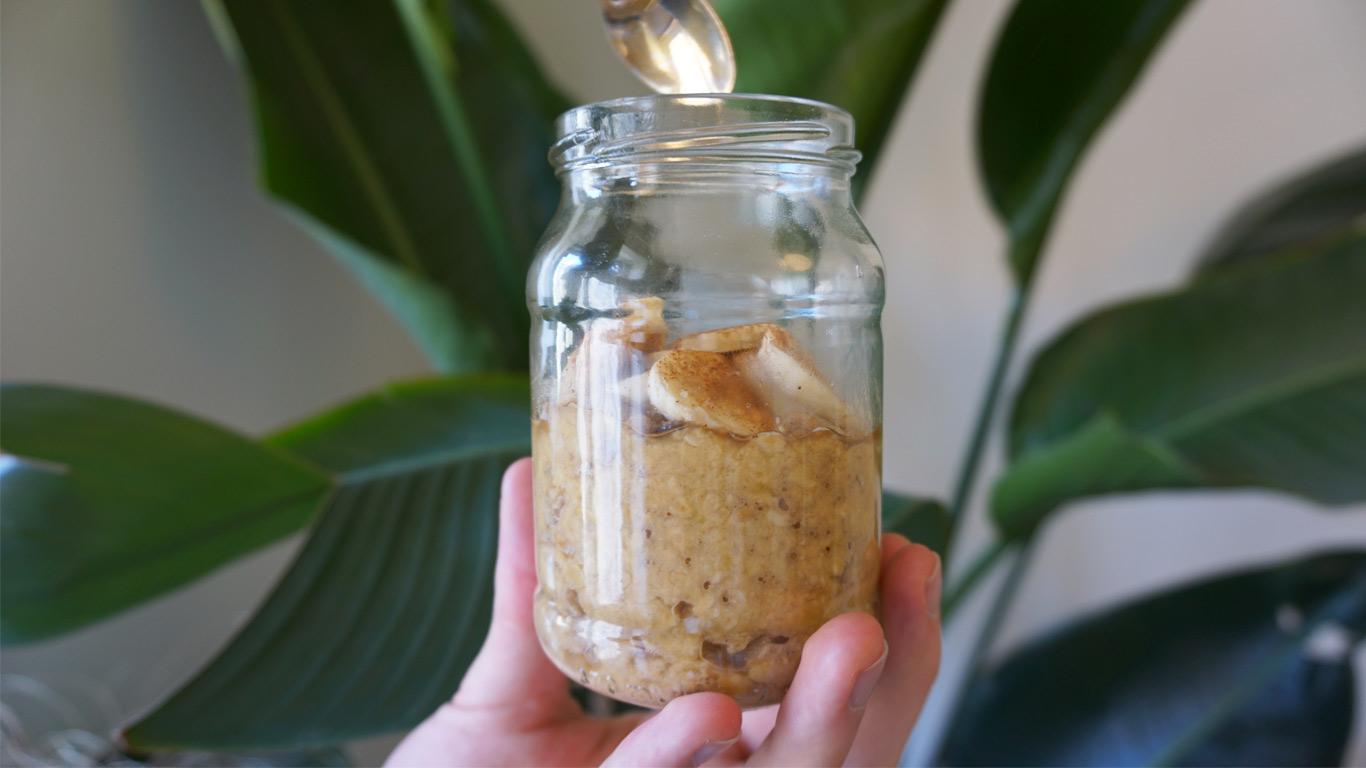 """Mão a segurar um frasco de vidro que contem papas de aveia com banana e canela como """"topping""""."""