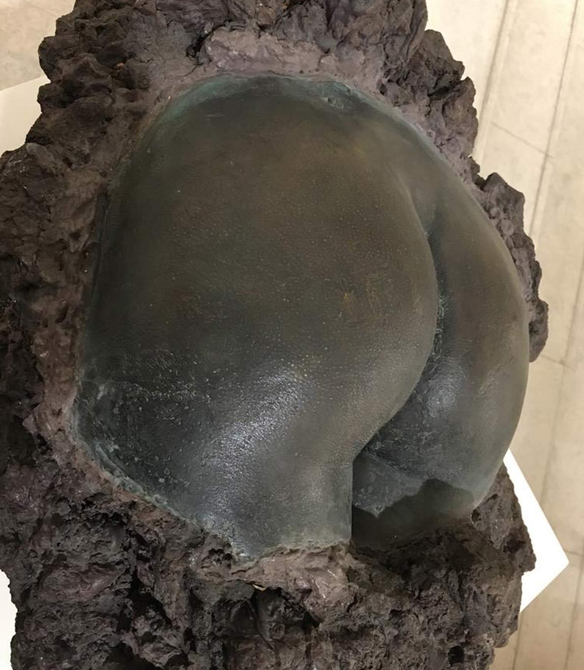 Escultura de um rabo humano construída à base de pedra vulcânica e bronze.