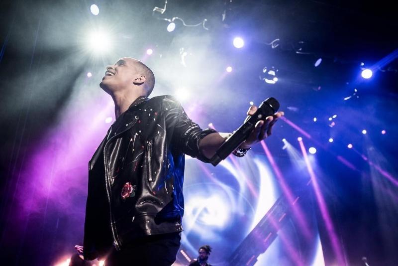 Na imagem podemos ver o cantor a sorrir, com o microfone na mão e luzes brancas e roxas no palco.