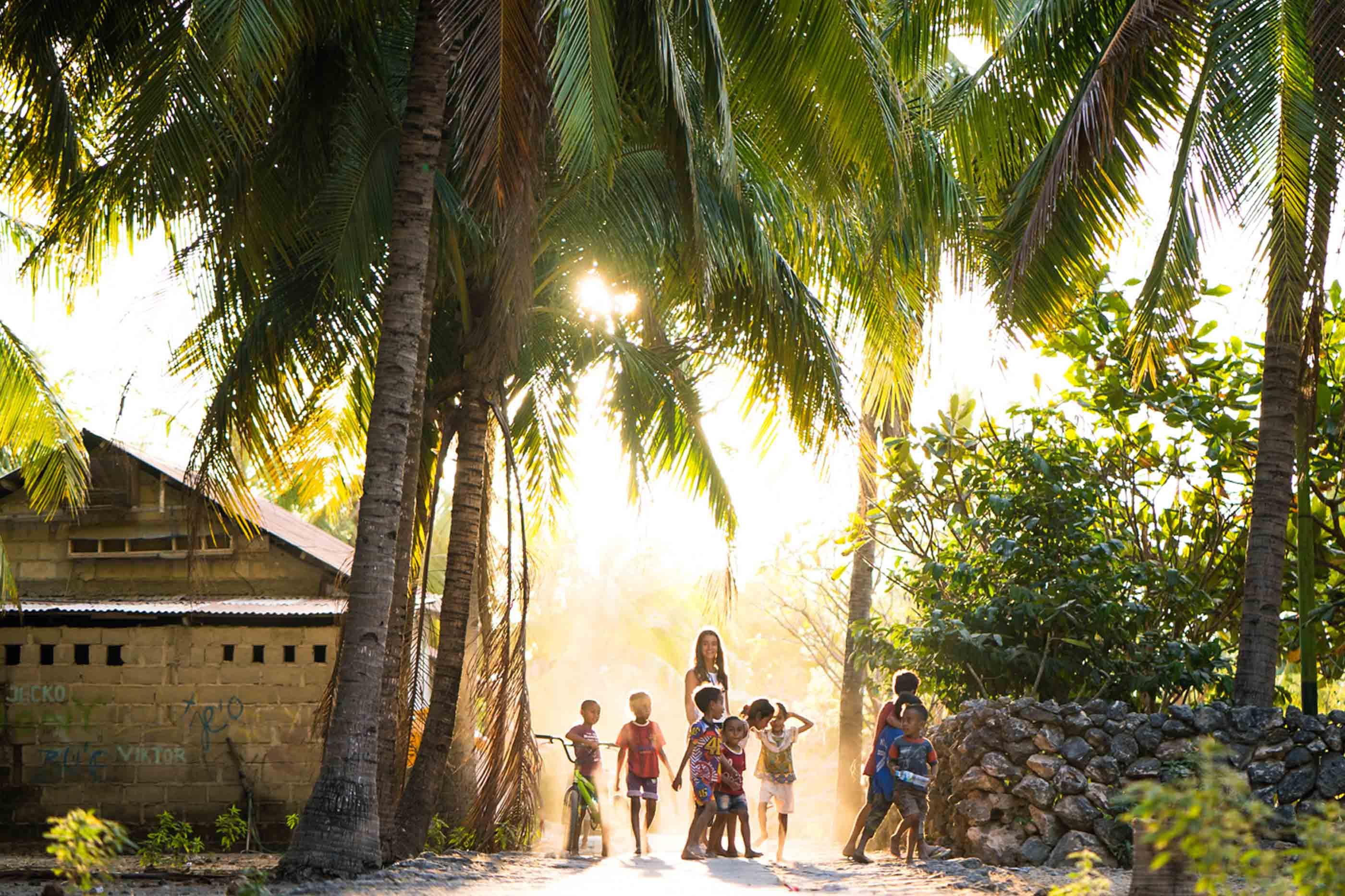 Paisagem tropical com palmeiras à volta e uma casa do loado esquerda da imagem. No centro, crianças e uma senhora.