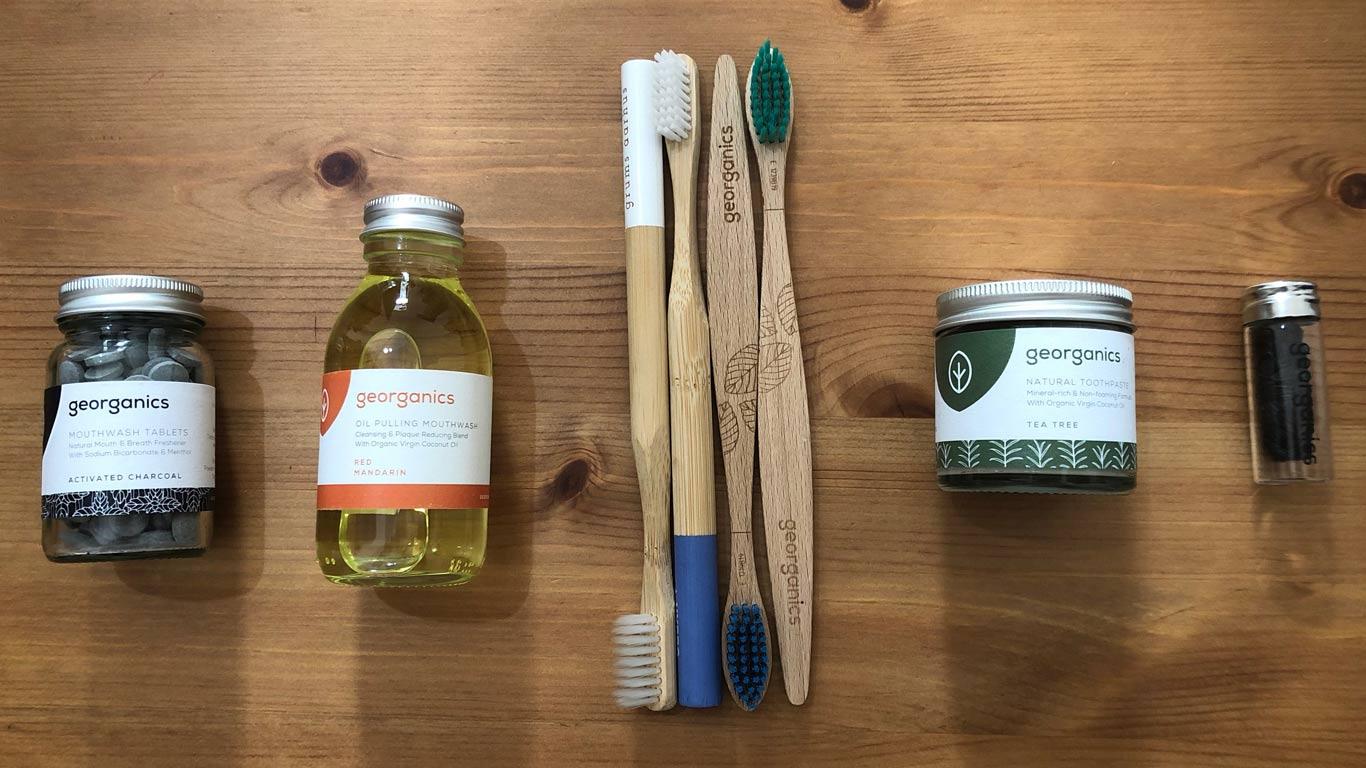 Escovas de dentes de bambu. Ao lado direito, pacote com elixir em pastilhas e elixir líquido. Do outro lado, pasta de dentes e fio dentário preto.