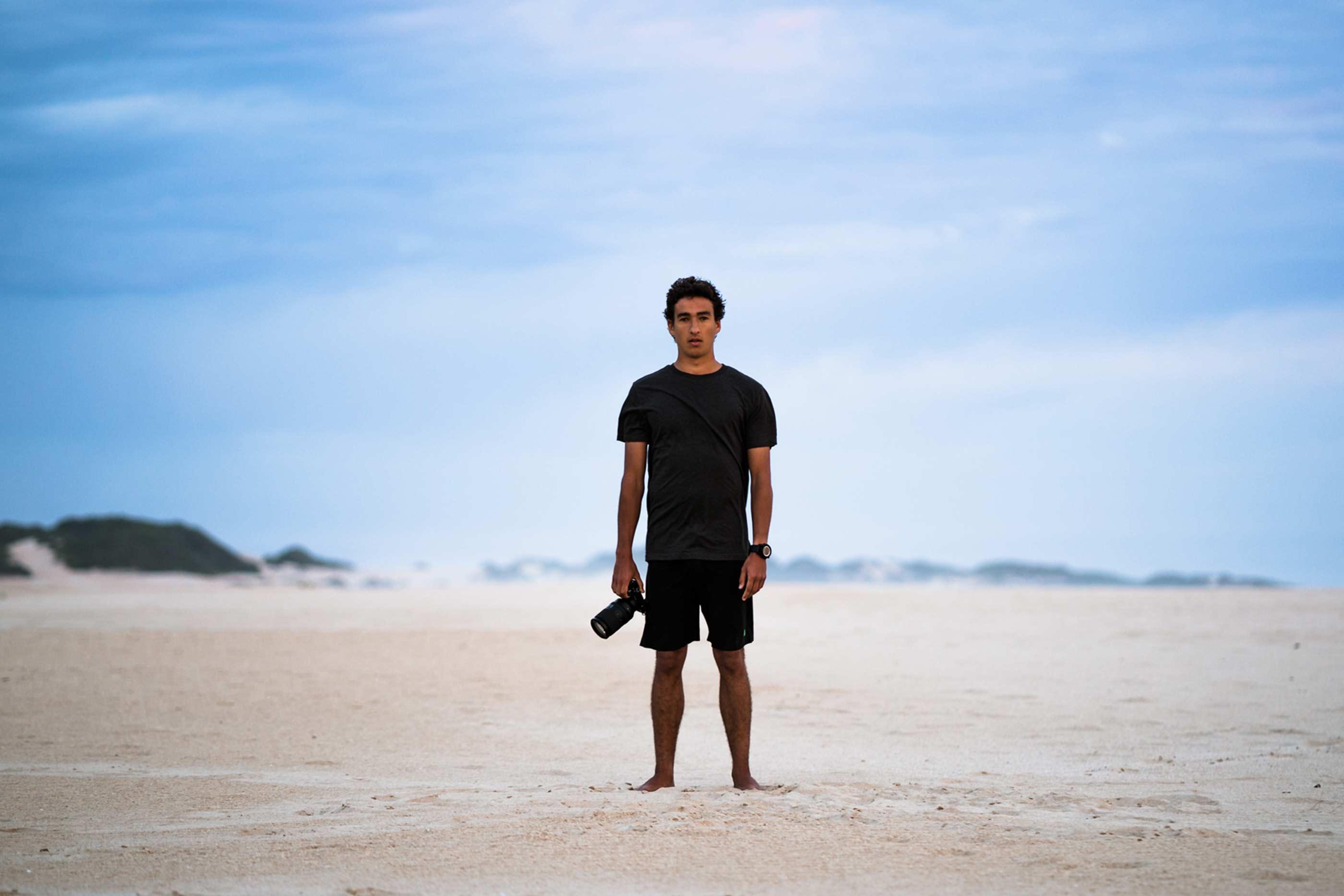 Rapaz, em pé, no centro da imagem, com máquina fotográfica na mão. No fundo, areia e céu azul.