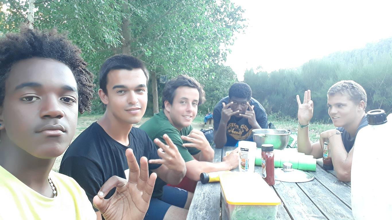 Cinco rapazes, sentados à volta de uma mesa com comida, a pousar para a fotografia e a fazer gestos com uma das mãos. Ao fundo, vegetação.
