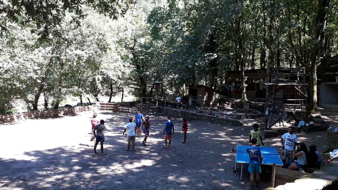 Jovens a jogar ténis de mesa e futebol, em terra batida. Ao fundo árvores e uma casa de madeira.