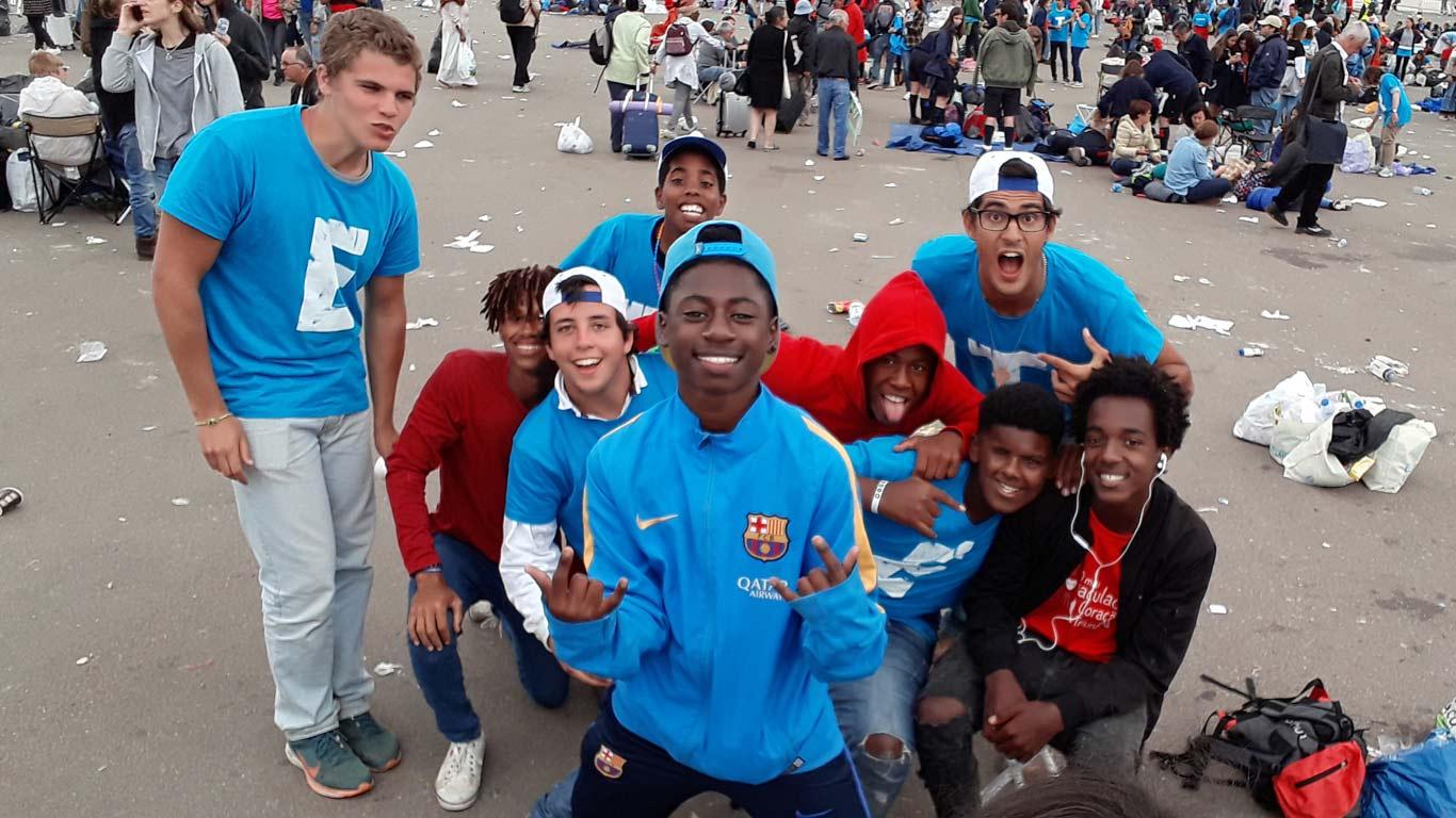 Vários rapazes, vestidos de azul ou encarnado, a pousar para a fotografia. Ao fundo, várias pessoas e lixo no chão.