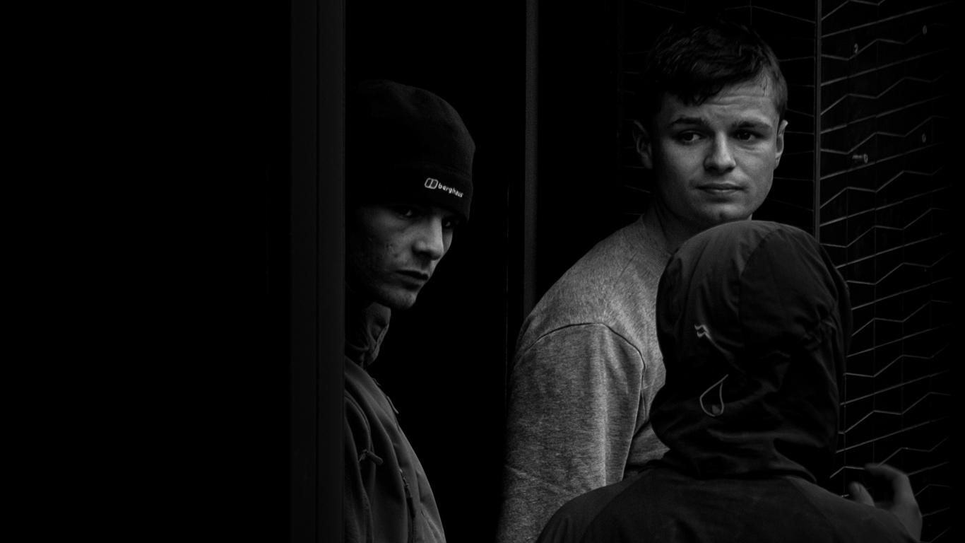 Três rapazes a comunicar. Dois virados para a câmara, outro de costas. Imagem a preto e branco.