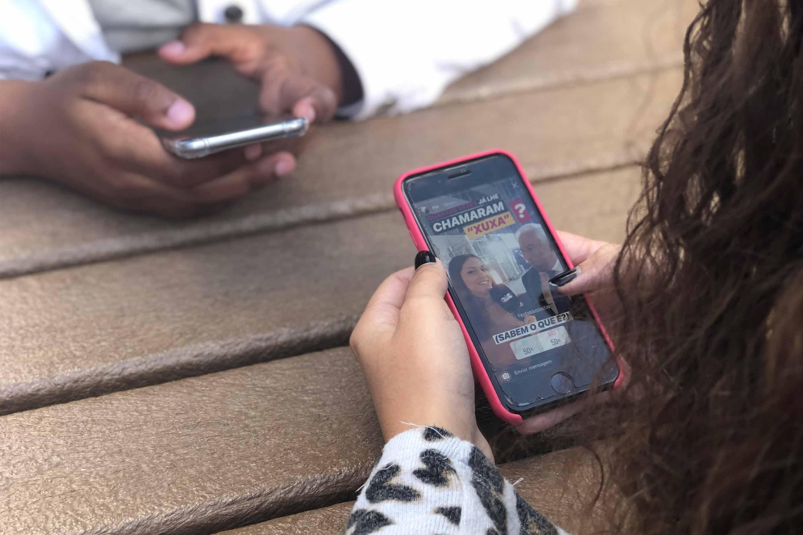 Duas pessoas a ver ver stories de Instagram onde Diana Duarte entrevista António Costa.