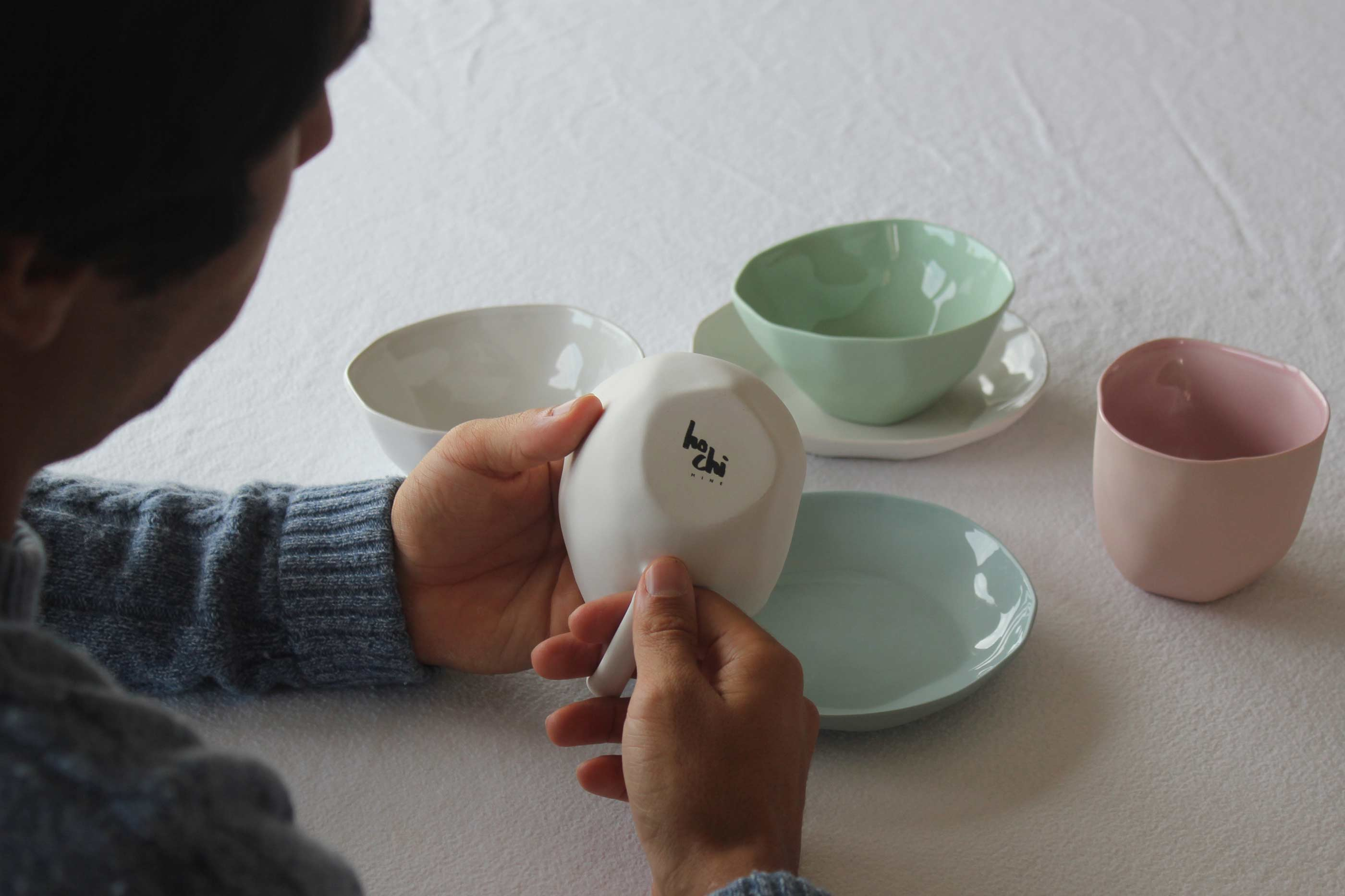 Peças de porcelana de várias cores, seguradas por um rapaz que evidencia o logotipo da marca.
