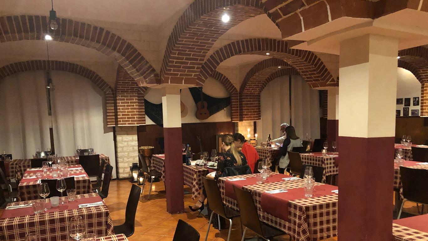 Sala grande com várias mesas e cadeiras dispersas, todas iguais, com uma toalha de mesa aos quadrados vermelhos e por cima, dois panos vermelhos onde estão dispostos talheres, copos e guardanapos. As cadeiras, por sua vez, são pretas e as pernas são de metal. Podemos ver dois casais a jantar.