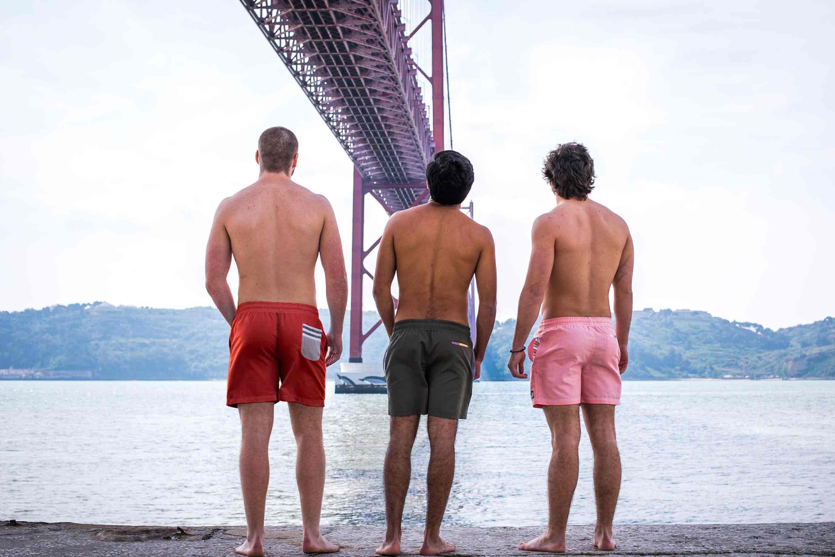 Ao fundo, o mar, colinas e por cima a ponte 25 de abril. Três rapazes de costas com calções de banho de cores diferentes.