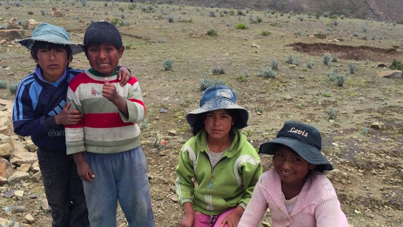 Quatro crianças numa planície no Lago Titicaca. Uma delas põe o polegar para cima. No chão, um pano com pedras por cima. Ao fundo, montanhas.