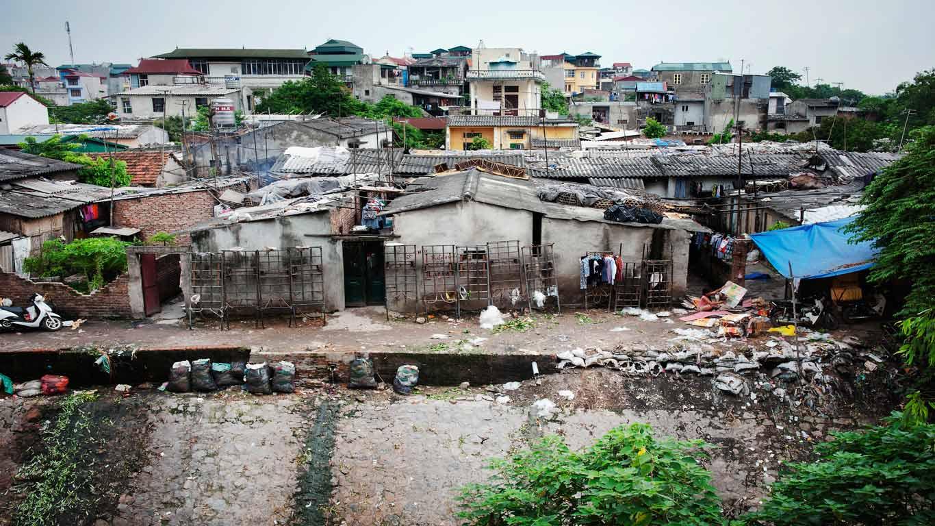 Bairro degradado, com lixo no chão e muitas casas degradadas. Diversidade de cores.