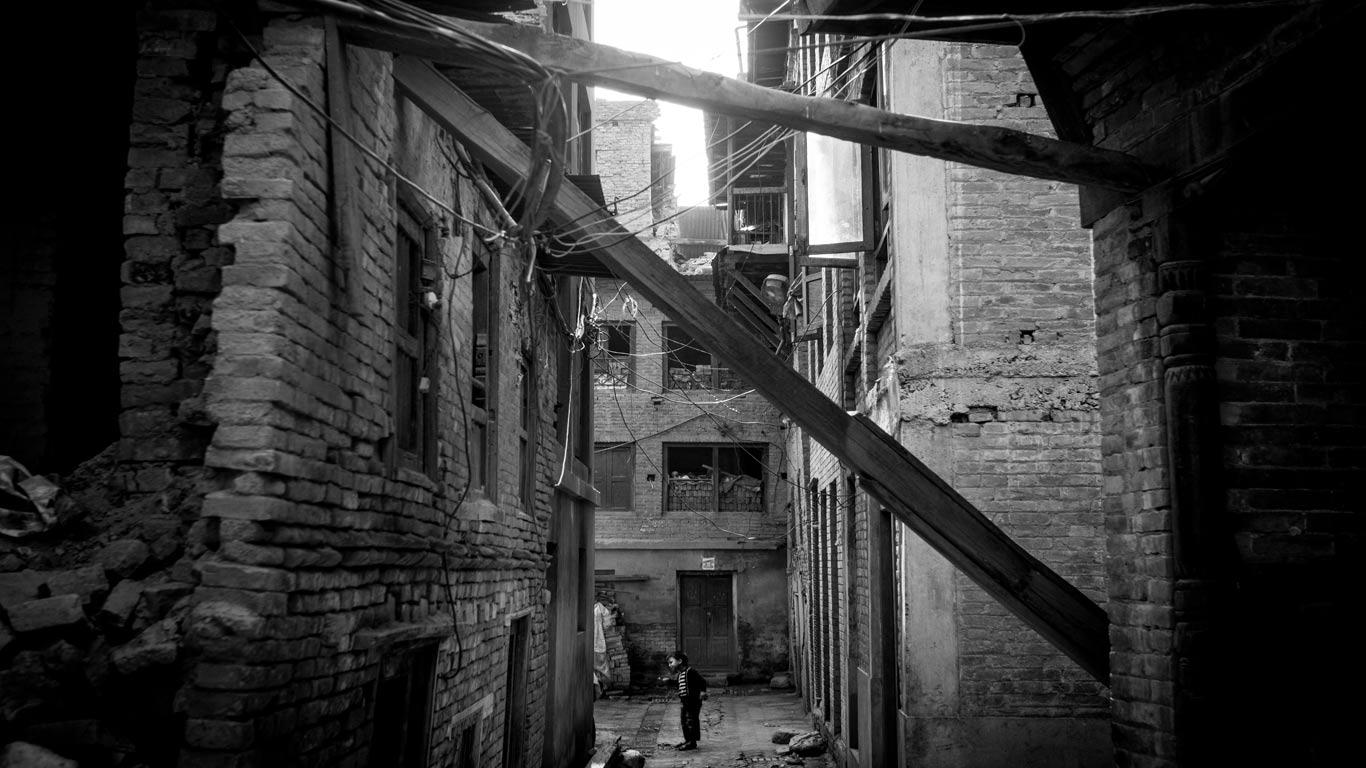 Prédios em ruínas, com colunas a atravessá-los e janelas cobertas por tijolos. No centro em baixo, uma criança a lavar os dentes. Imagem a preto e branco.
