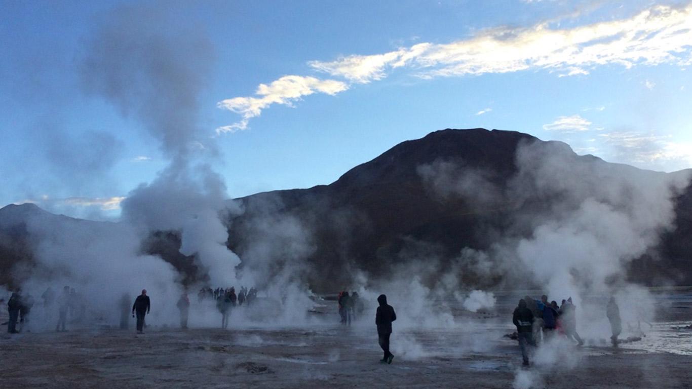 Géiseres de Tatio no Deserto do Atacama. Turistas a caminhar por entre os géiseres. Vapor a ascender. Chão molhado ao pé dos jatos de água. Ao fundo, montanhas