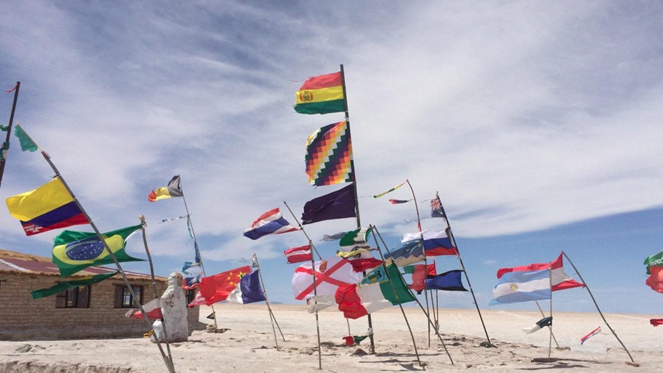 Bandeiras de diferentes países no Salar de Uyuni a esvoaçar ao vento. Algumas estão rasgadas. Muro com degraus em pedra. Ao fundo, uma casa em pedra.