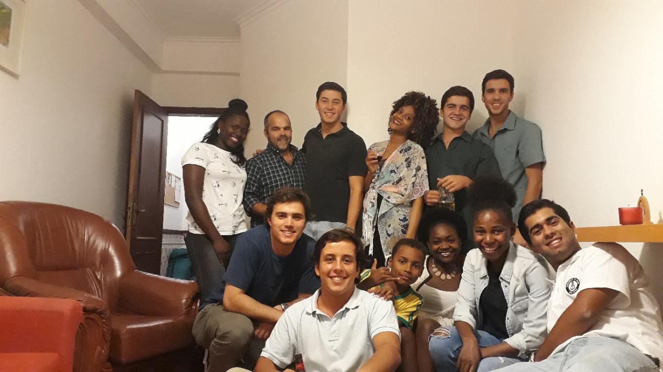 Grupo de pessoas de diferentes raças, a sorrir, numa sala de estar.