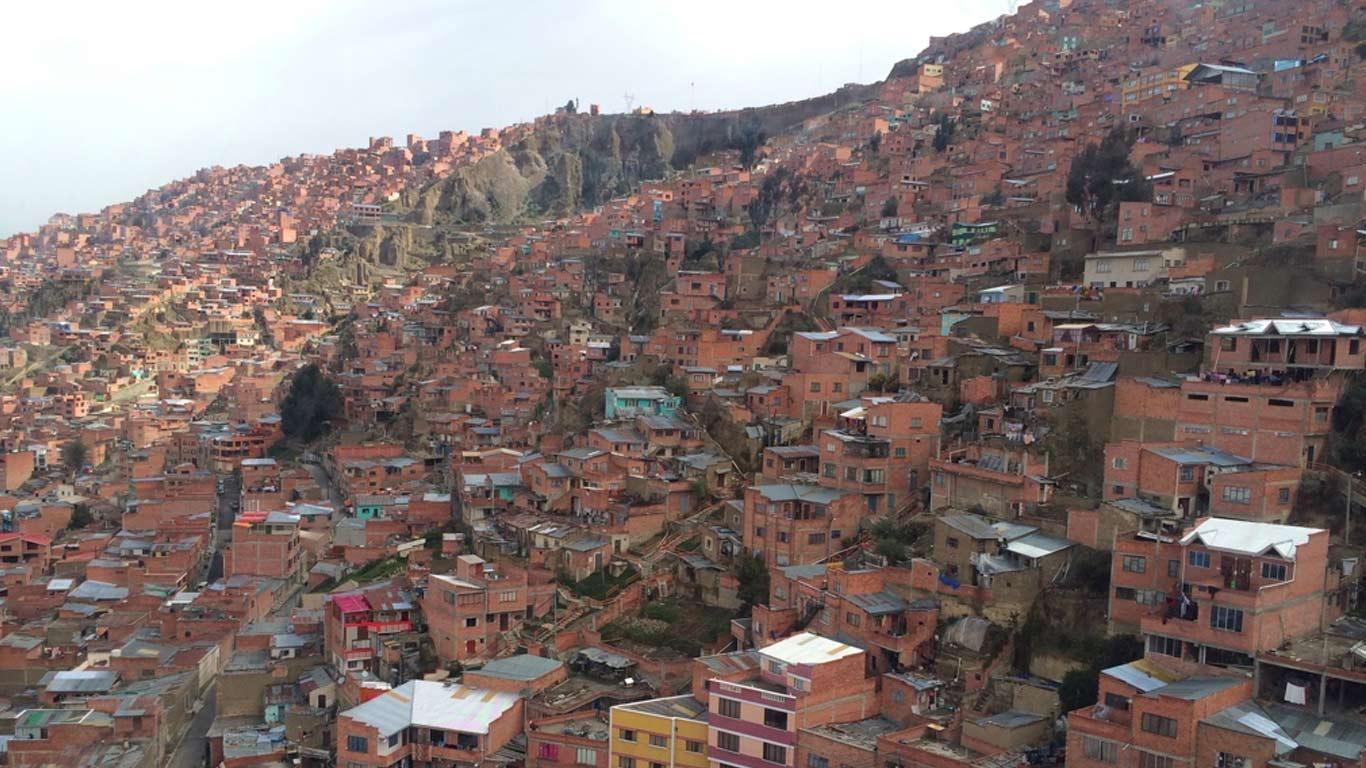 Favela da cidade de La Paz, na Bolívia. Muitas casas construídas em tijolo numa montanha. Em primeiro plano, um campo de futebol e uma estrada.