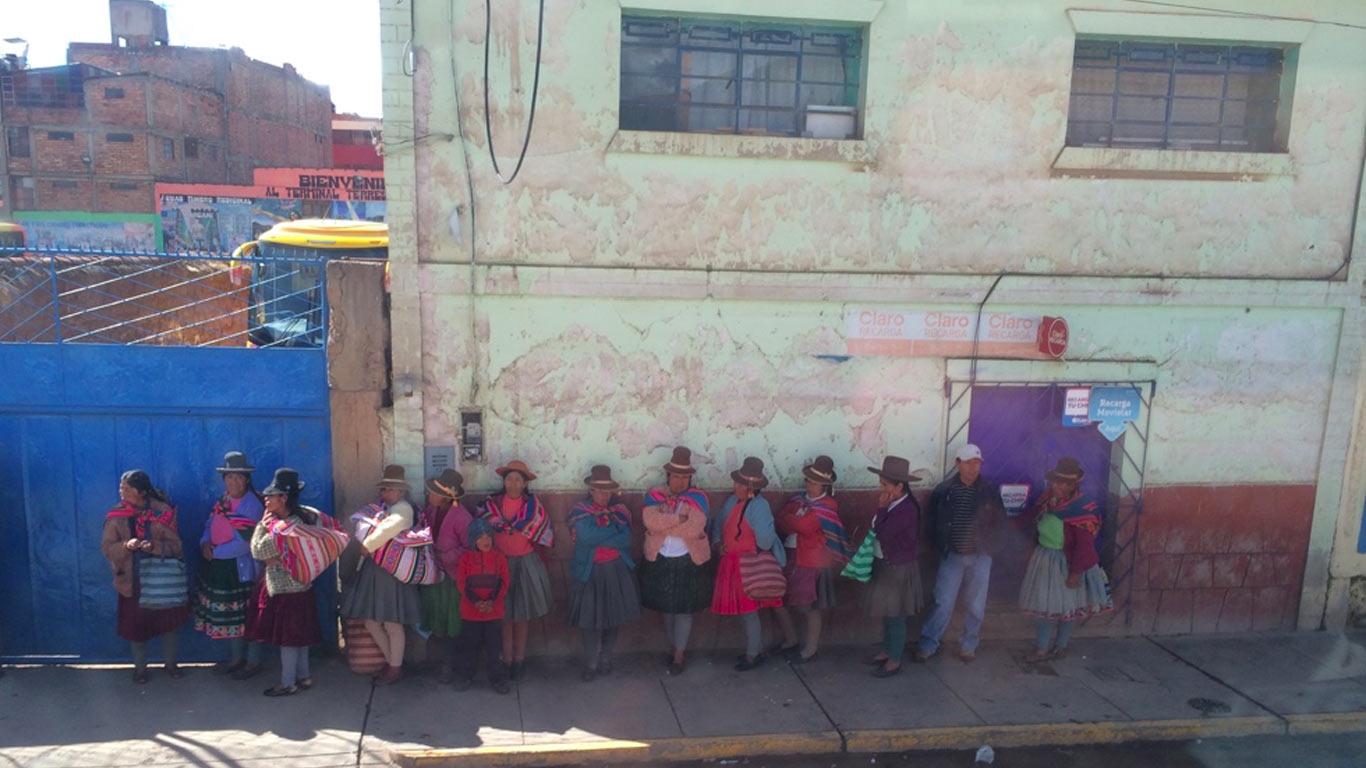 Doze mulheres e um homem de pé encostados a uma parede. As pessoas encontram-se à sombra. As mulheres estão vestidas com trajes tradicionais.