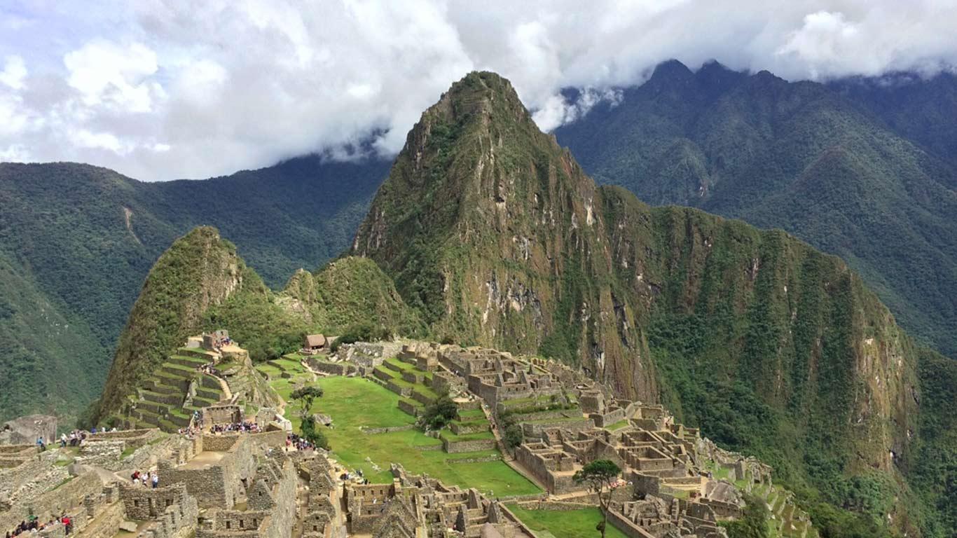 Ruínas da cidade de Machu Picchu no Peru. Muralhas e casas em pedra. Turistas a andar entre as ruínas. Ao fundo, montanhas que tocam nas nuvens.