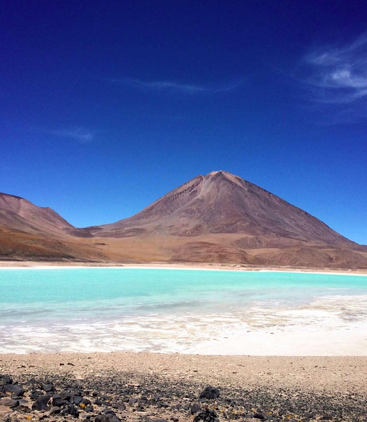 Salar de Uyuni na Bolívia. Em primeiro plano, rochas pretas e areia. Ao fundo, duas montanhas. No meio, um lago azul claro com acumulações de sal junto à areia.