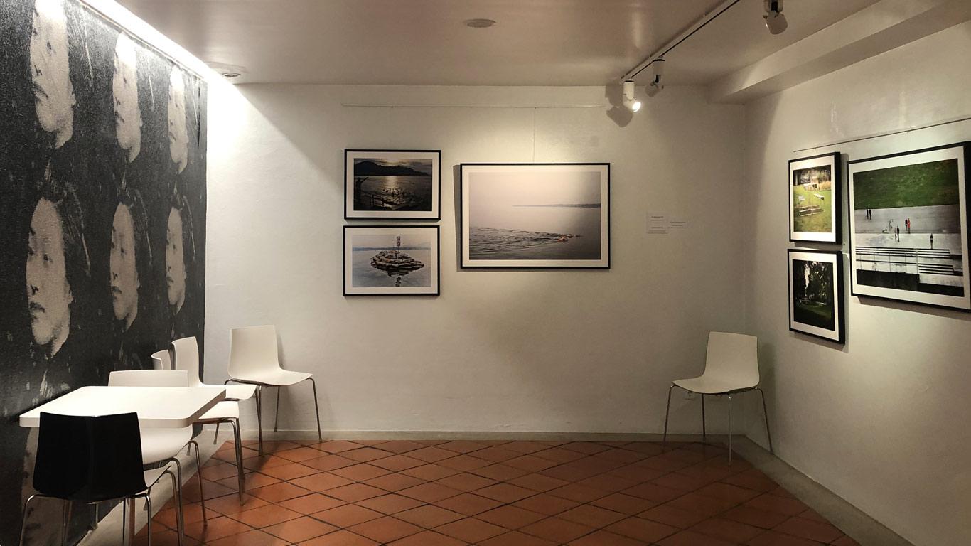 Três paredes, duas delas com fotografias de uma exposição, a terceira, é um moral com pequenos azulejos a formar os rostos de mulheres a preto e branco.