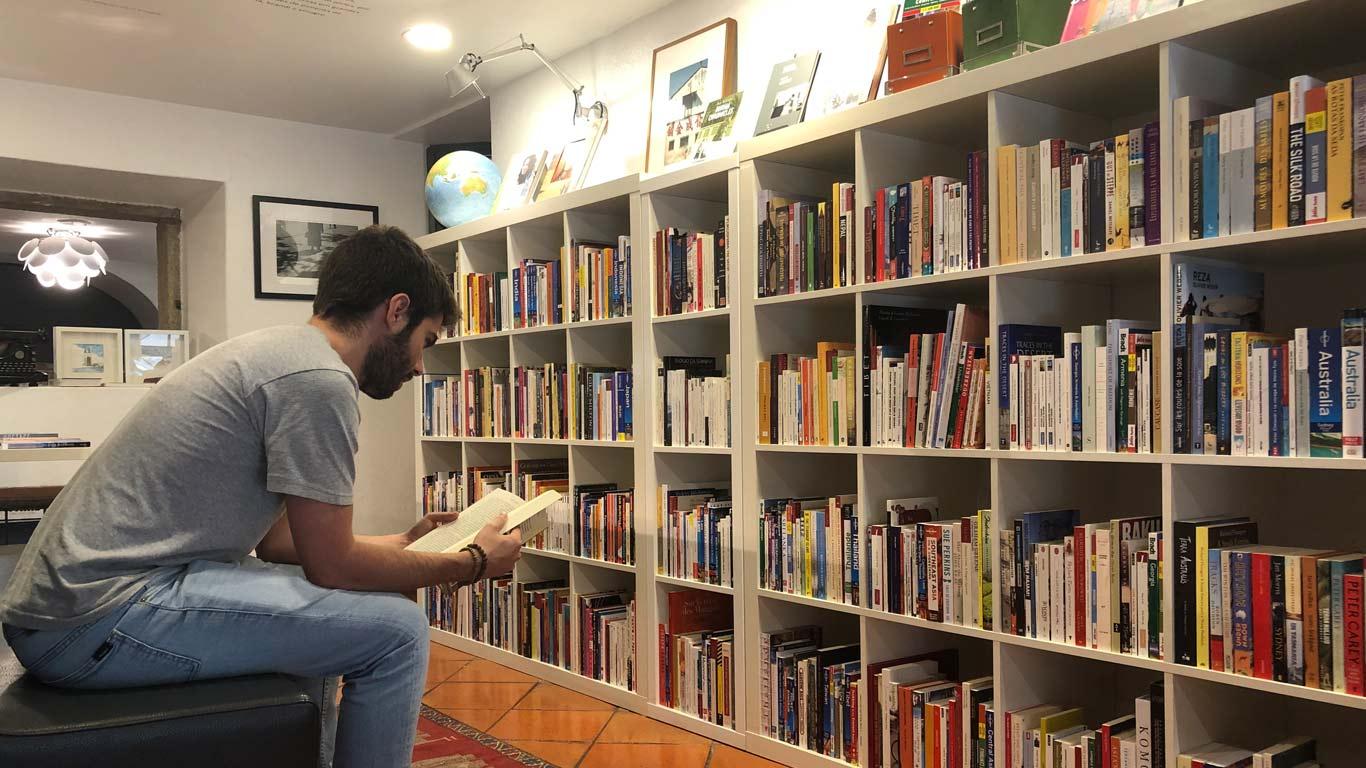 Leitor sentado num sofá, a ler um livro. Ao fundo, uma estante cheia de livros.