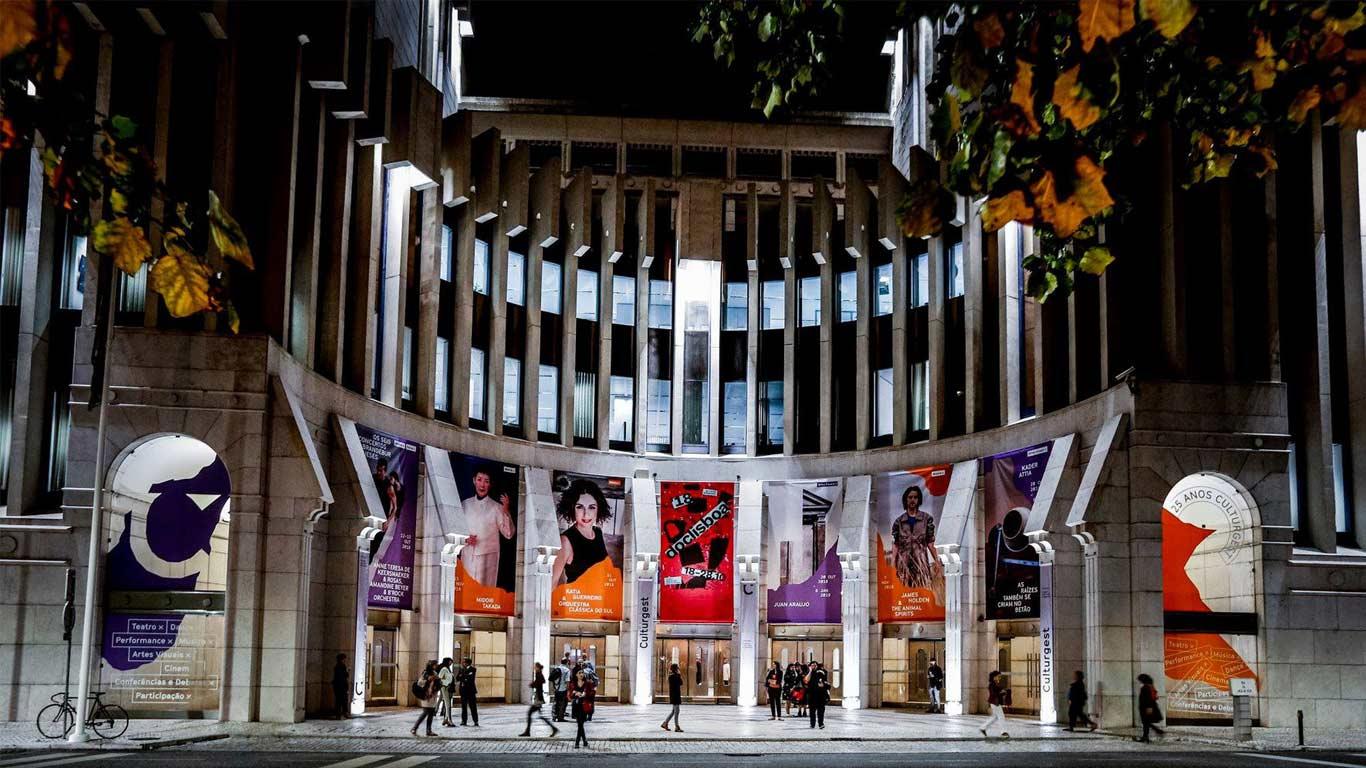 Fachada principal, de noite, com vários cartazes dos filmes e exposições presentes na fundação. Edifício redondo, com várias janelas e portas altas. Várias pessoas a entrar e sair do edifício