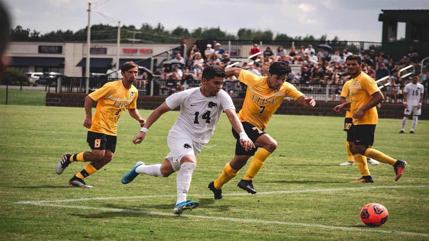 Três jovens a jogar futebol.