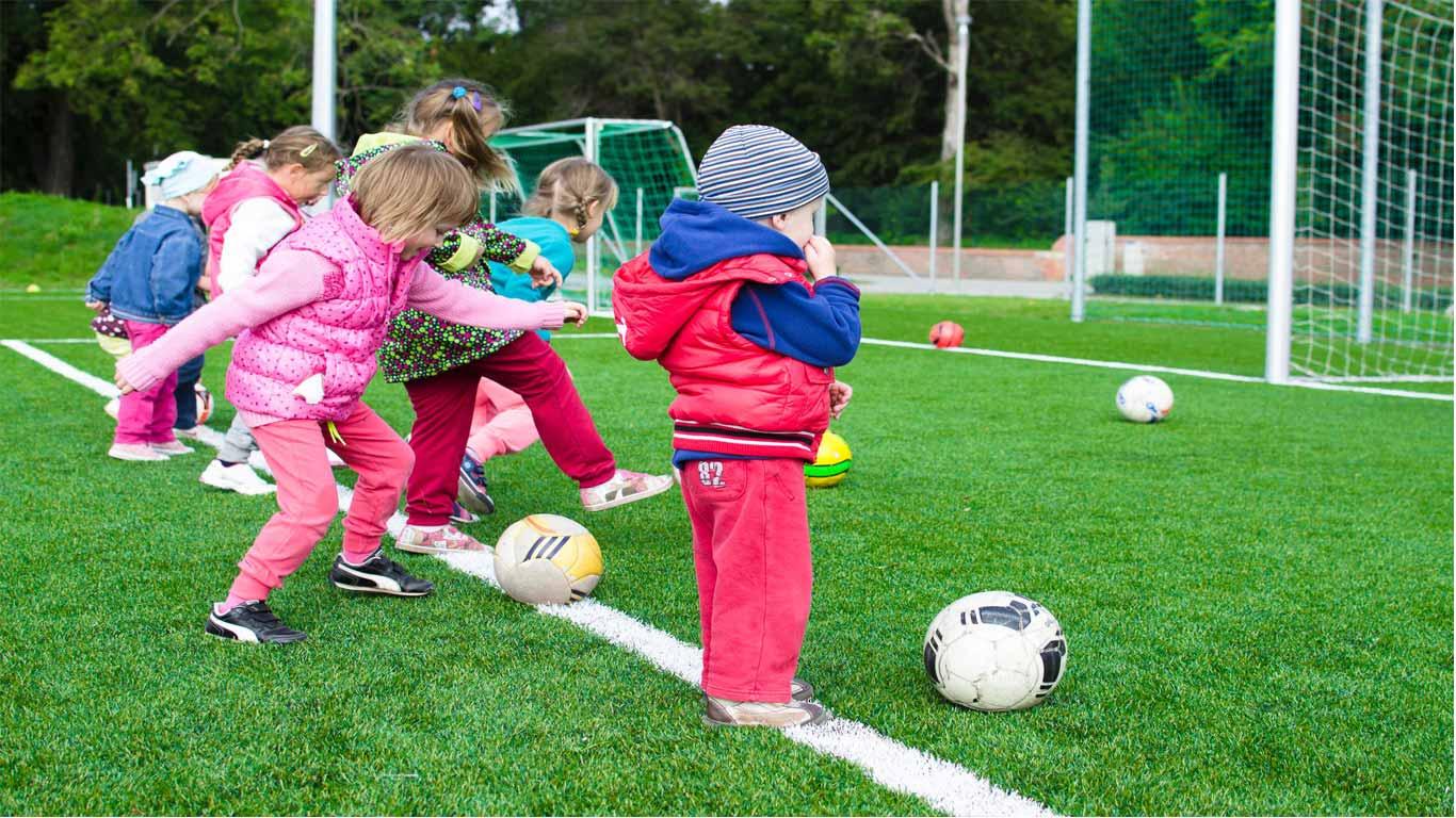 Várias crianças a jogar futebol num relvado.
