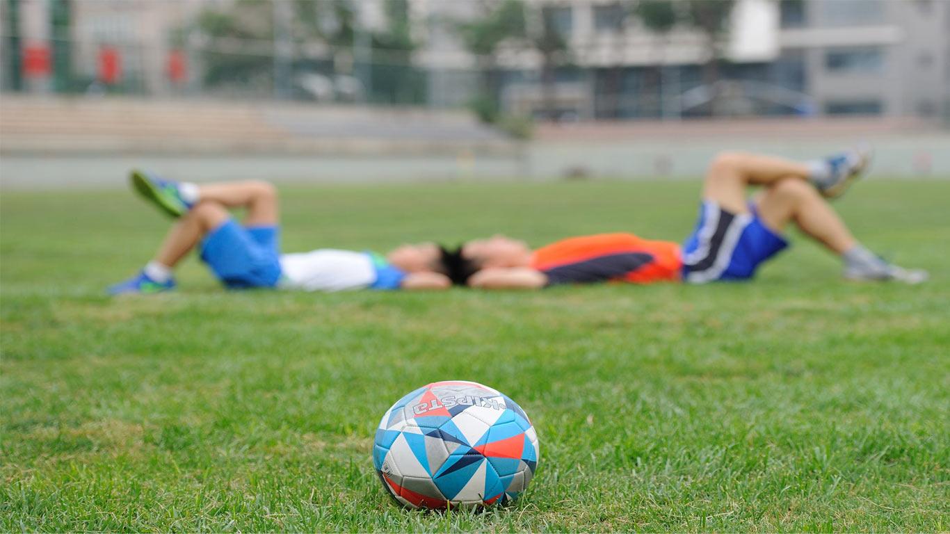 Dois jovens deitados no campo de futebol a fazer alongamentos, no seguimento de um jogo/ treino de futebol.