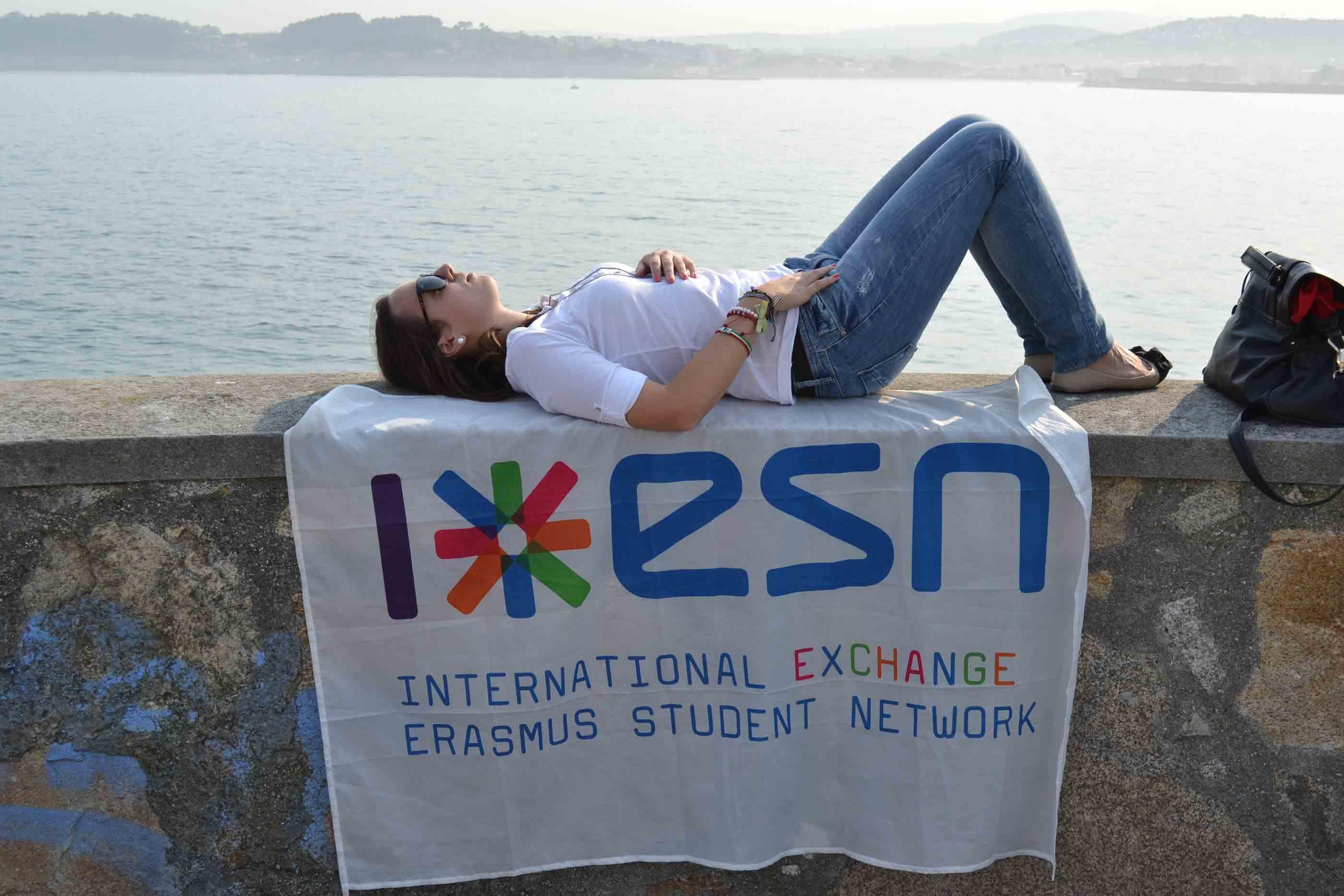 Rapariga a descansar deitada à beira rio em cima de um muro e da bandeira da ESN