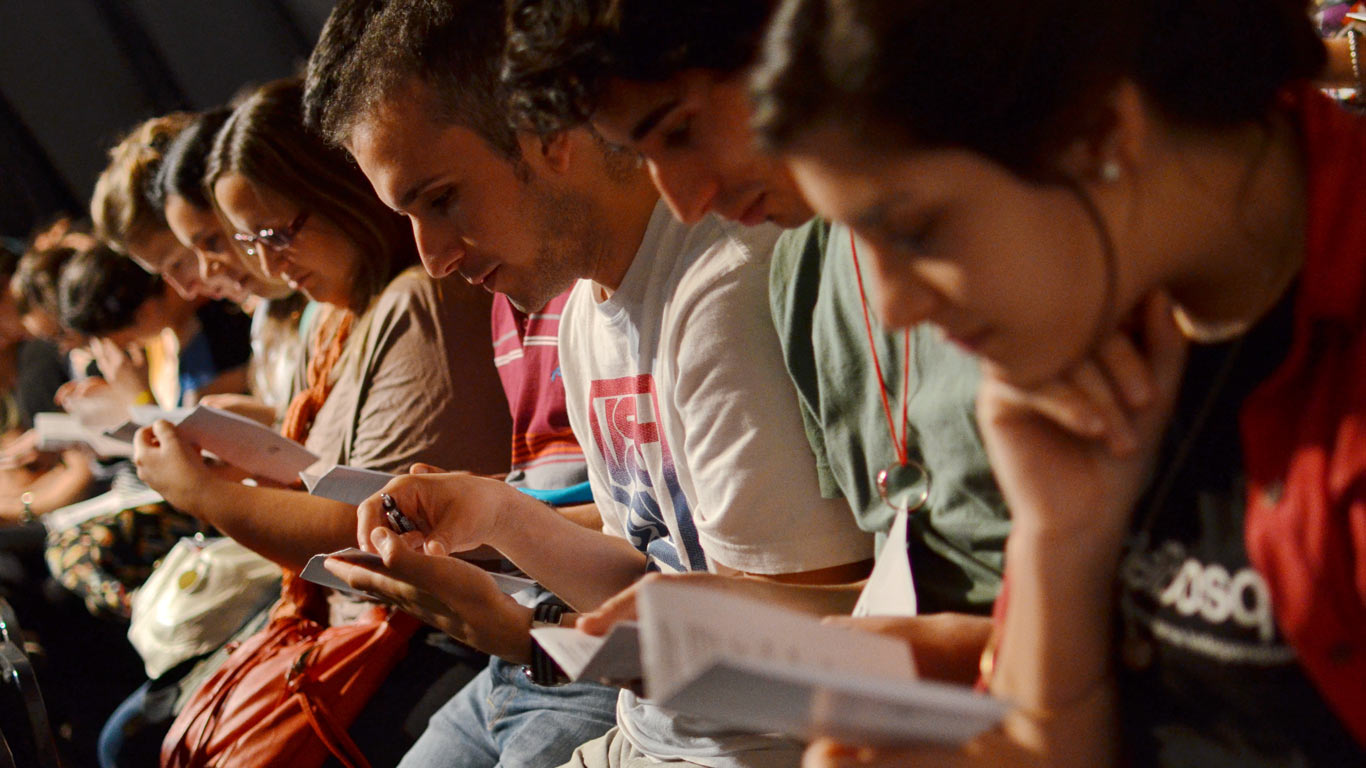 Pessoas sentadas lado a lado, a lerem boletins de informação.