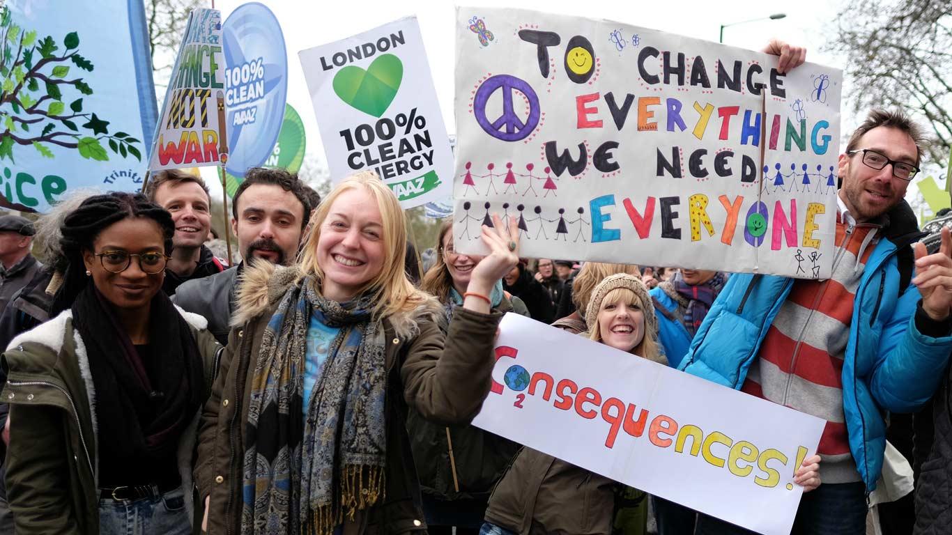 Pessoas de várias etnias juntas com ar alegre, erguendo cartazes contra as alterações climáticas.