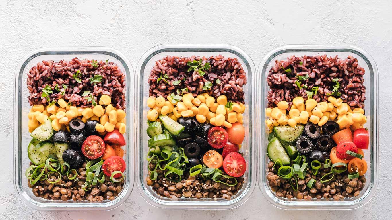 Três recipientes de vidro que contêm comida saudável no seu interior.