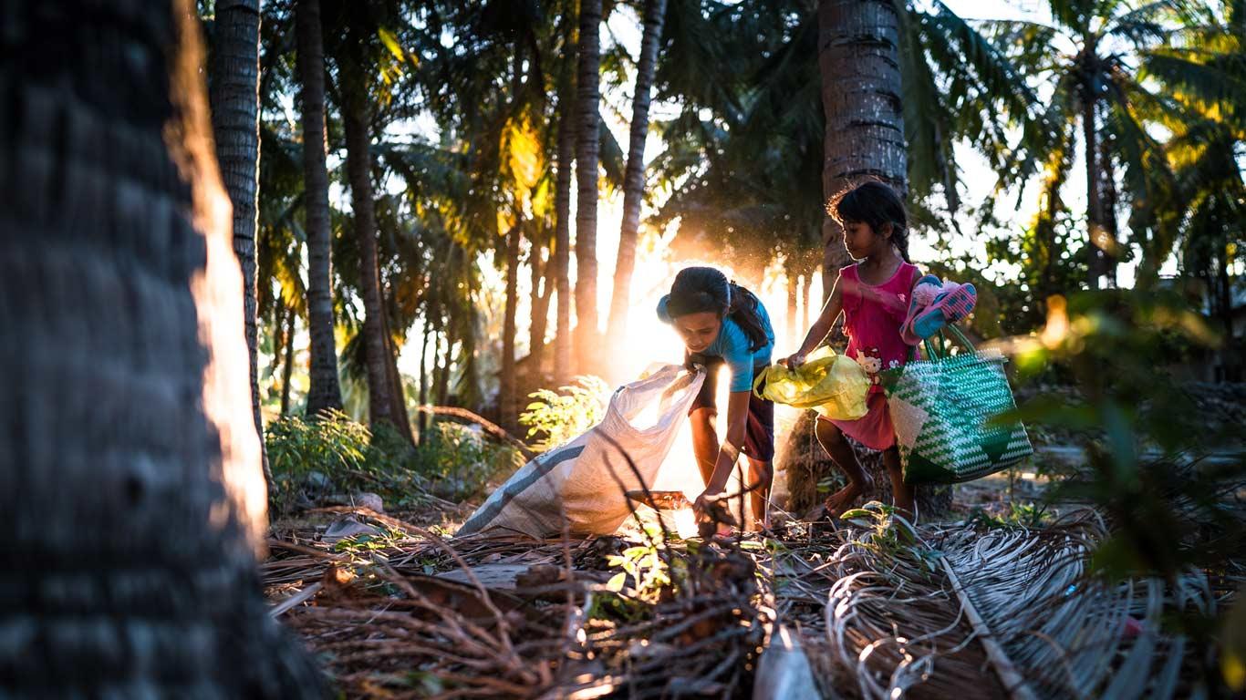 Duas crianças a apanhar lixo numa zona tropical. Raios de luz