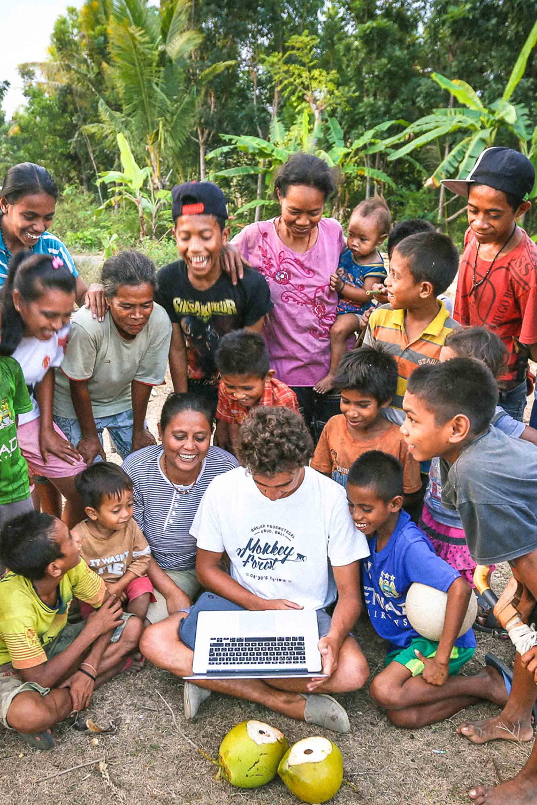 No centro, rapaz com um computador, rodeado por jovens e adultos que observam o computador e riem. À frente, dois côcos, no fundo, árvores.