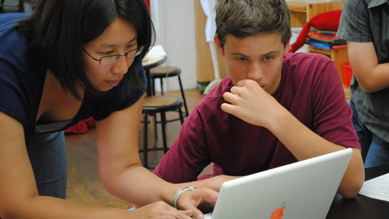 Professora a dar instruções num computador a um aluno numa sala de aula.