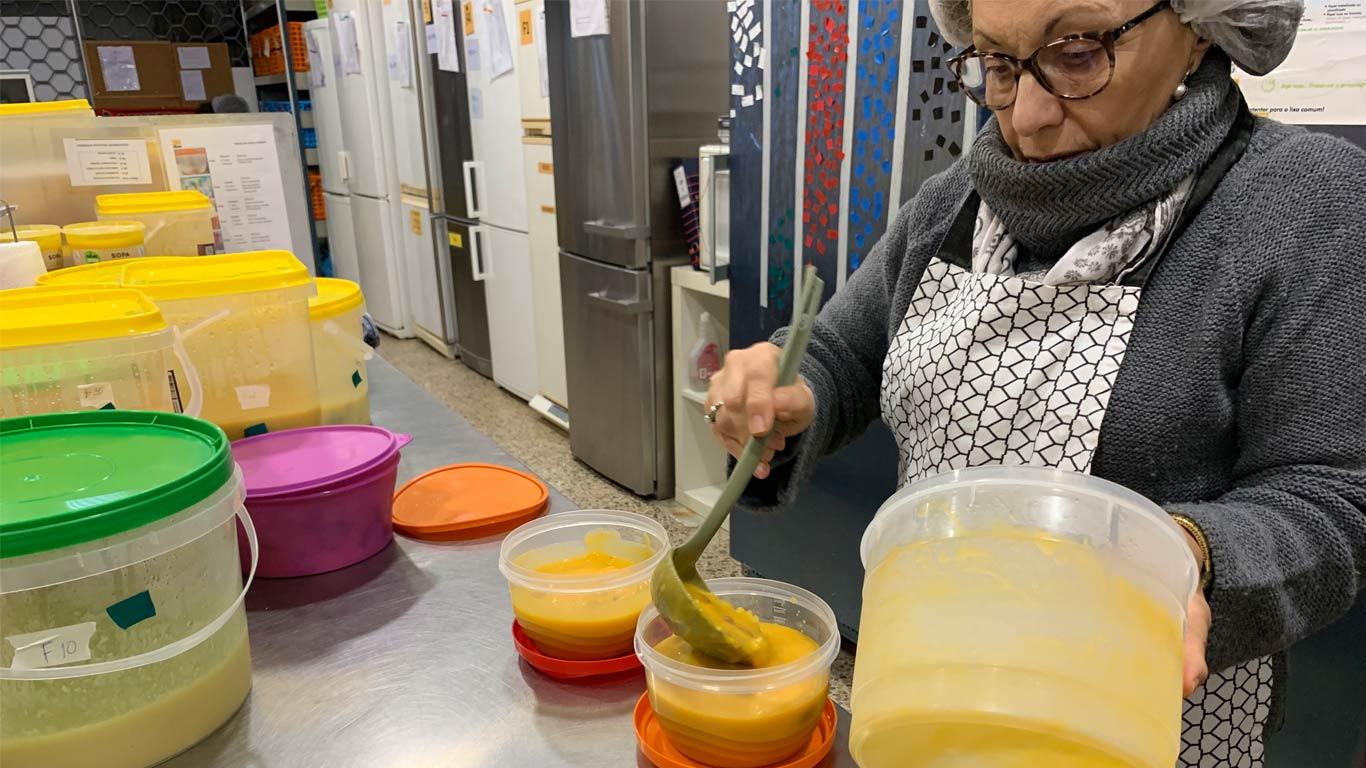 Funcionária a distribuir sopa pelas várias marmitas.