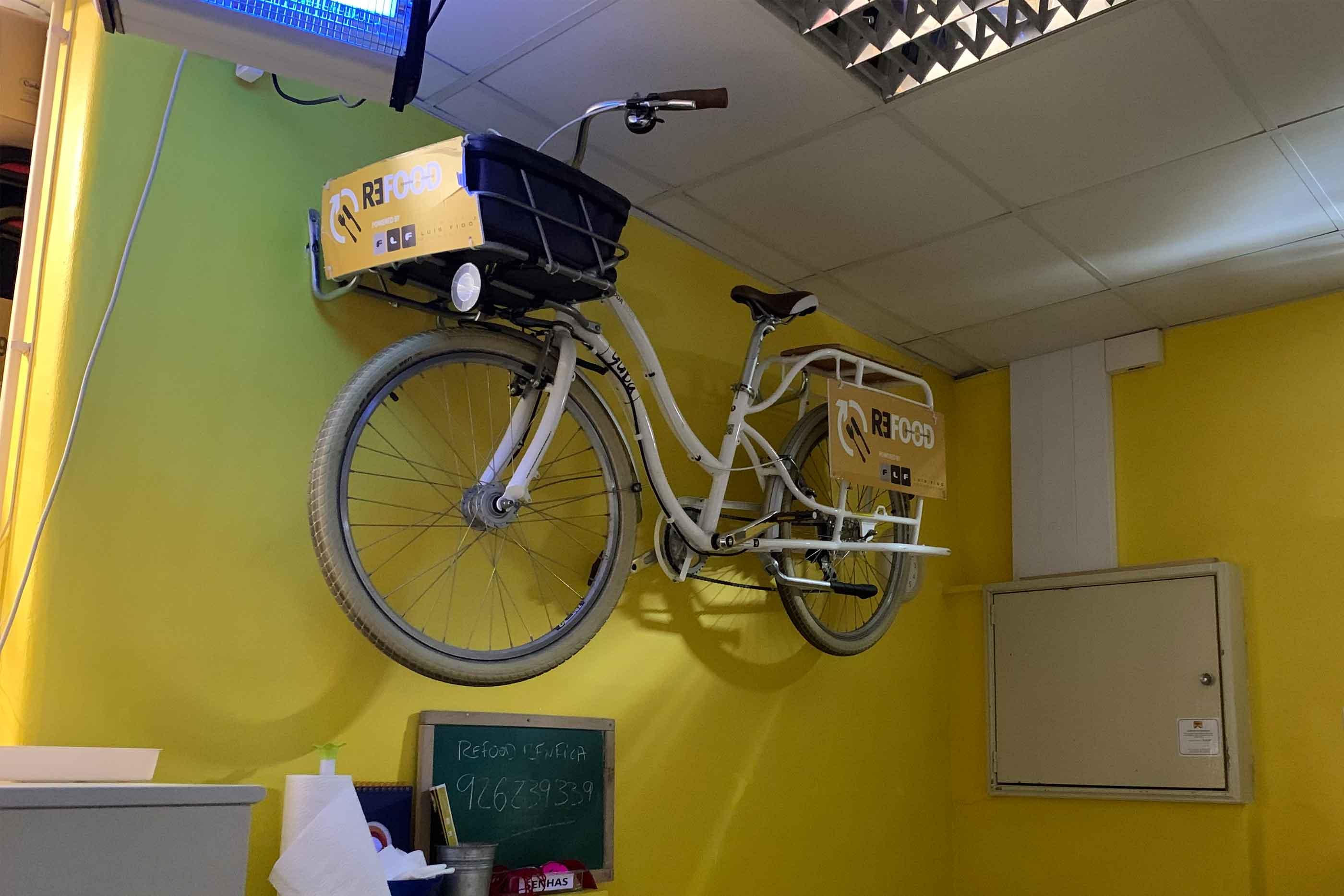 Bicicleta com cesto de distribuição da Refood pendurada na parede amarela e um quadro com o número de telefone da empresa.