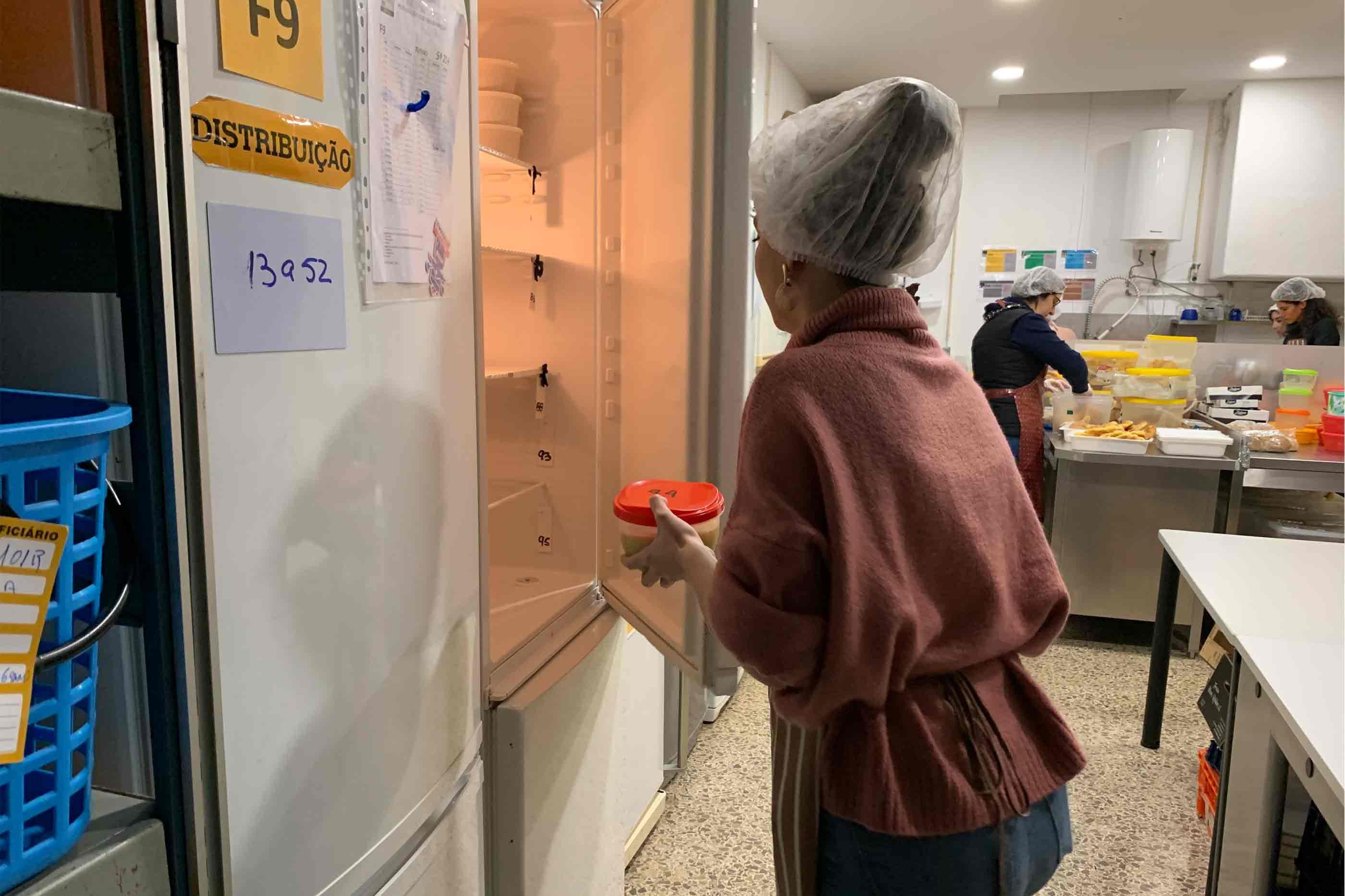 Voluntária a colocar as marmitas nos frigoríficos, onde ficam armazenadas até à hora de distribuição.