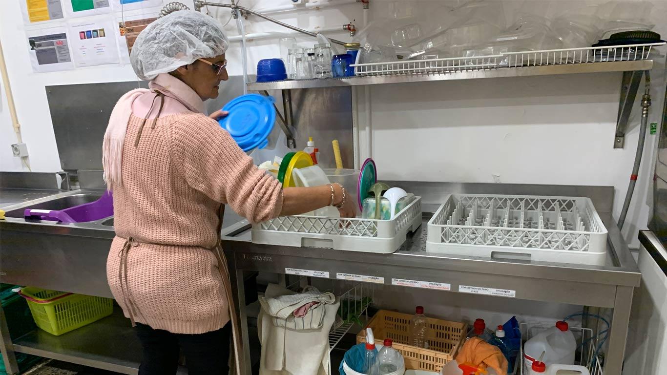 Voluntária a lavar os vários utensílios de cozinha