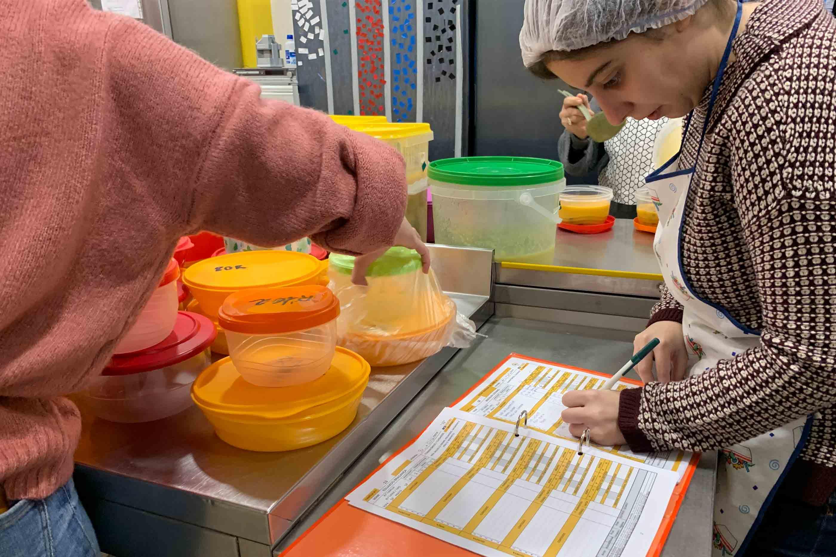 Voluntária a verificar e anotar a distribuição de refeições de cada beneficiário.