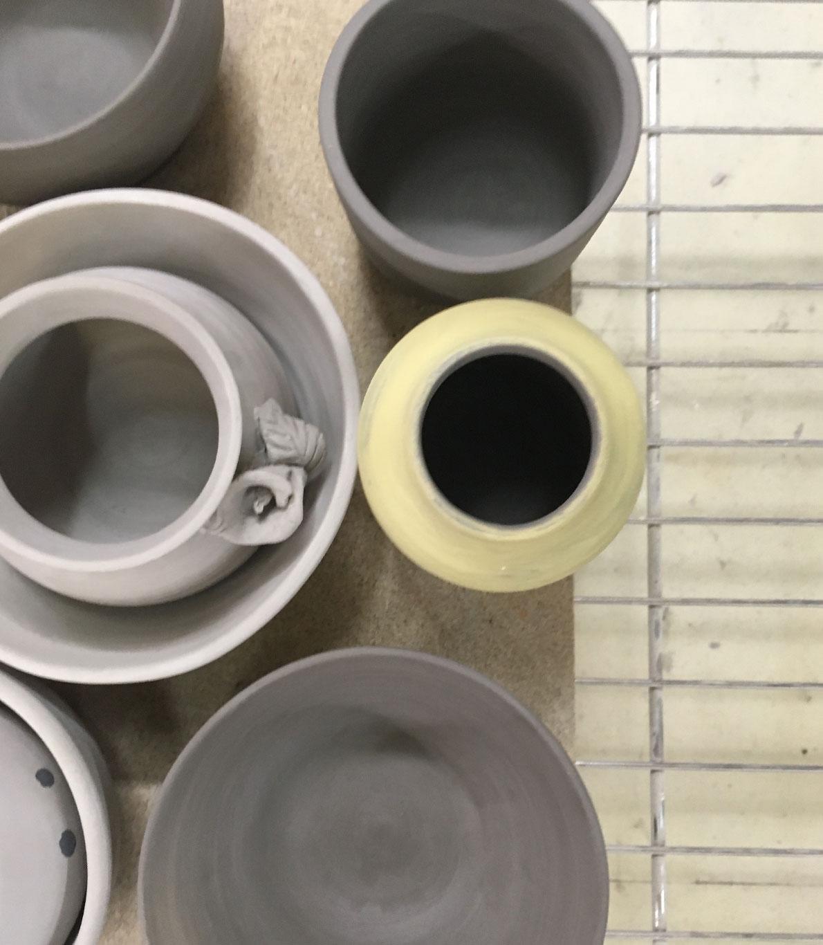 Peças de cerâmica, copos, tigelas e vasos, a secarem numa prateleira.