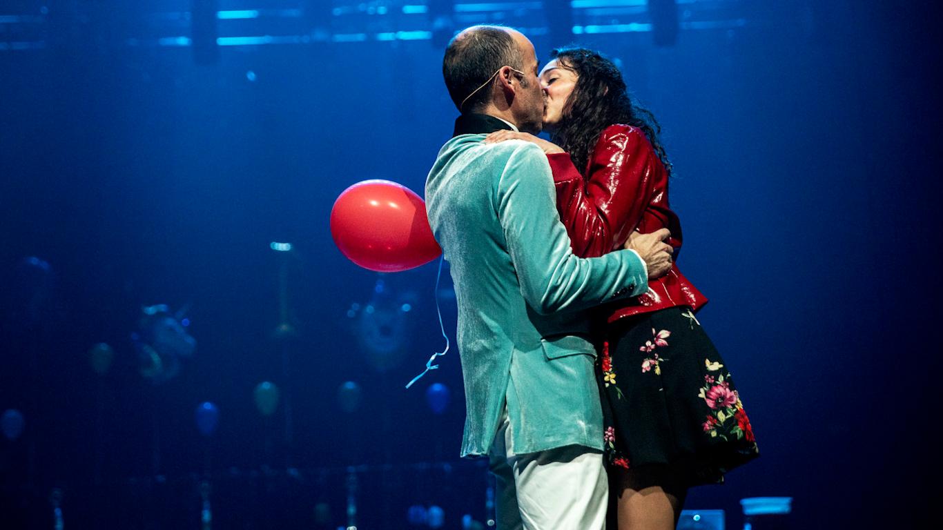 Personagem masculina e feminina em casa, a representar um casal apaixonado e aos beijos