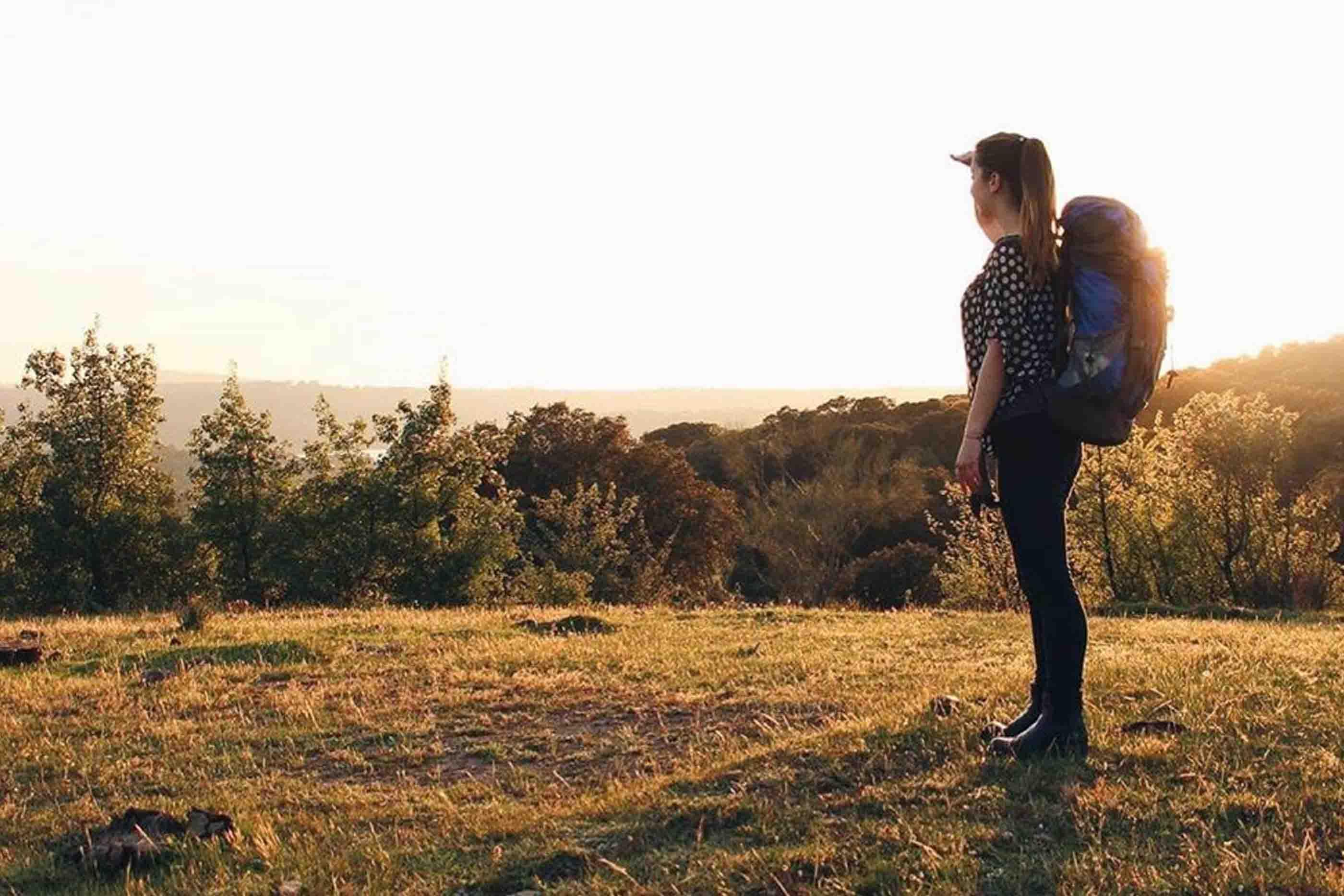 Rapariga com mochila de campismo às costas a olhar para a paisagem