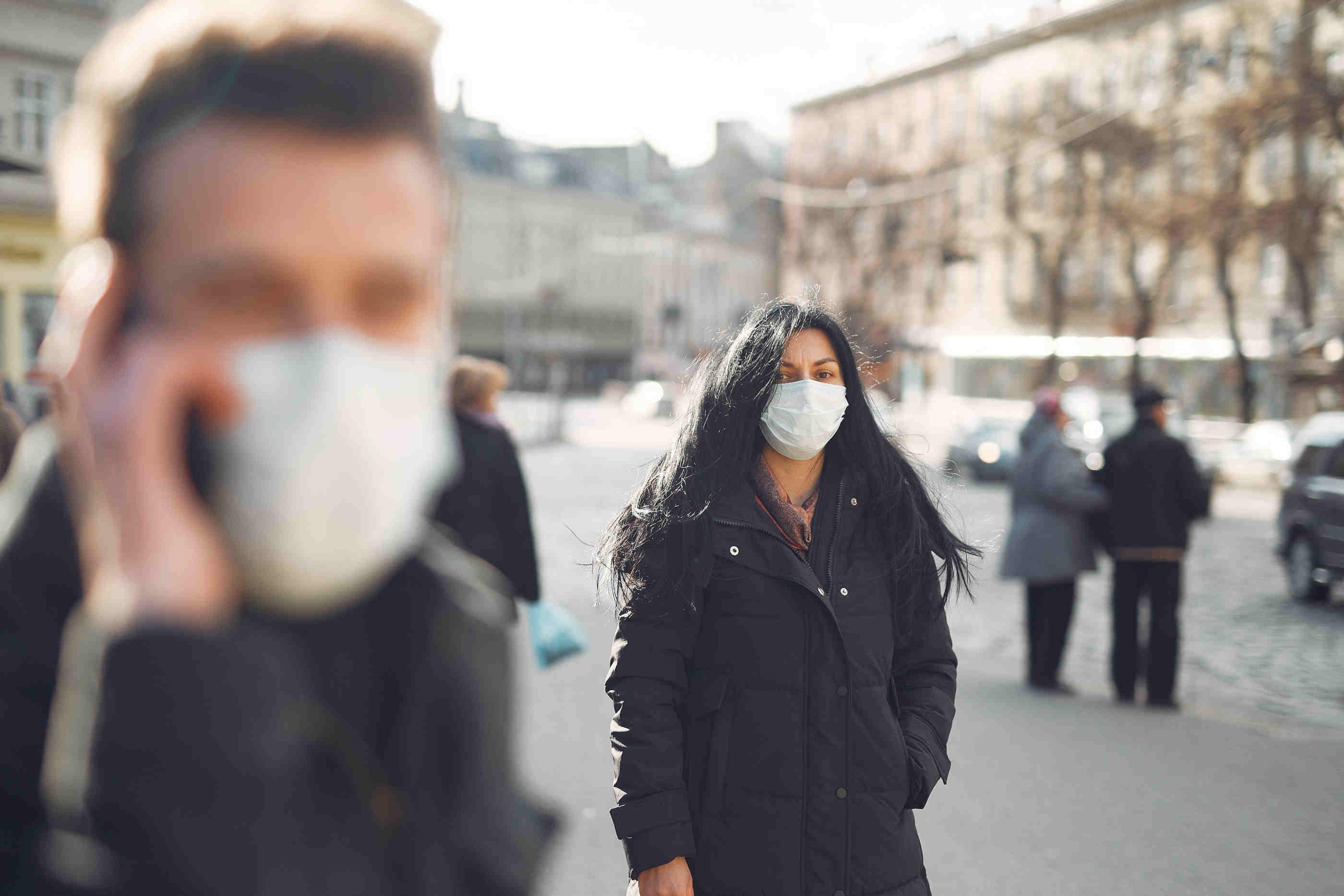 Pessoas na rua com máscaras cirúrgicas na cara
