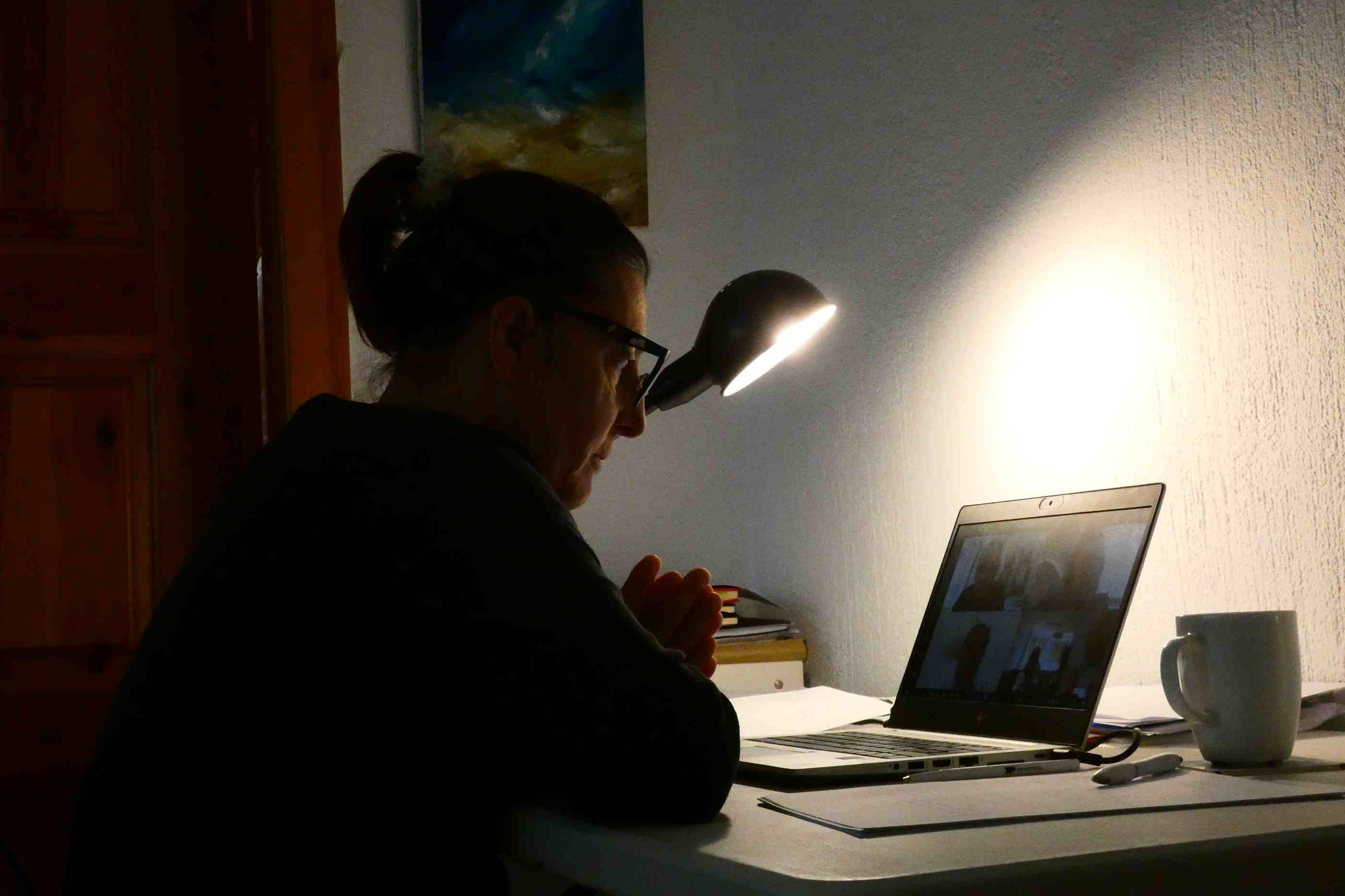 Mulher sentada à secretária a participar numa videoconferência por meio do portátil.