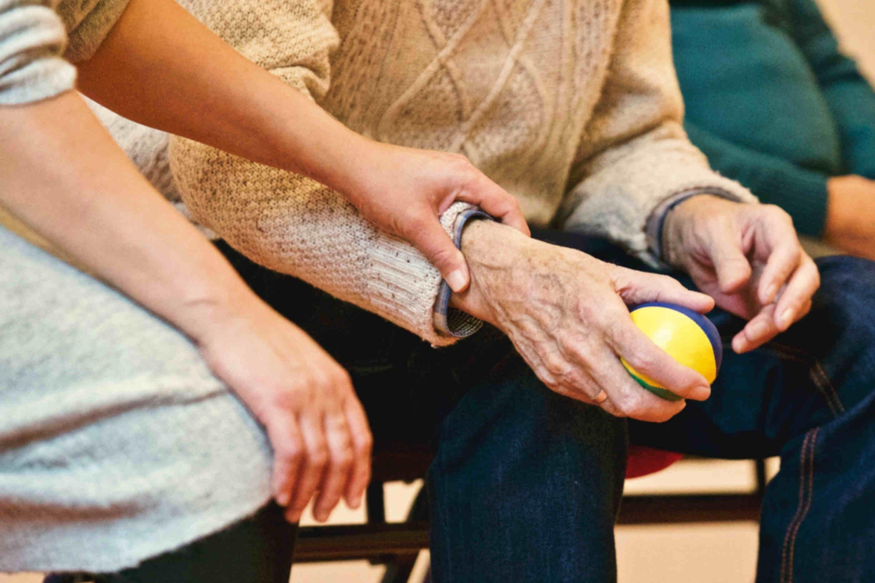 Senhora e idoso sentados lado a lado. Senhora mede a pulsação do idoso enquanto este último agarra uma bola anti-stress para as mãos.