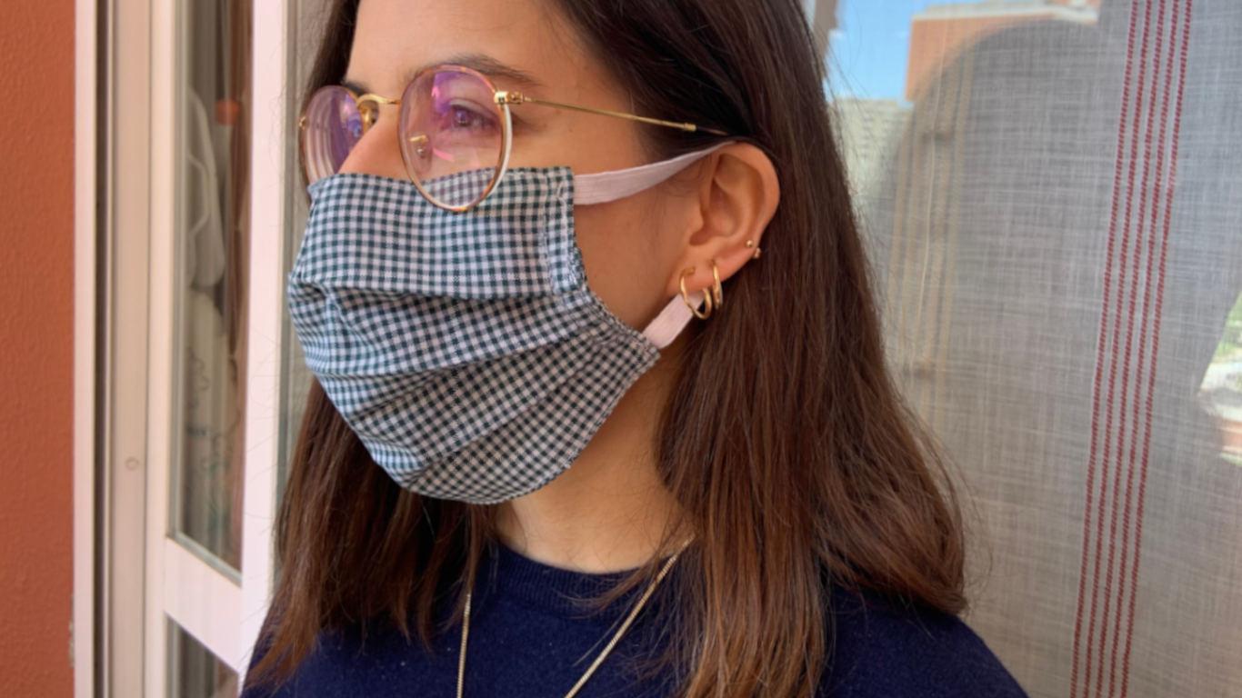 Rapariga a utilizar uma máscara de uso público a tapar o nariz e a boca