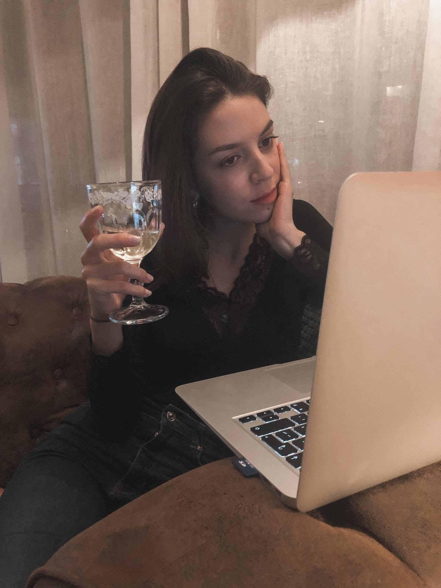Rapariga sentada no sofá, em frente ao computador, com um copo de vinho branco na mão.